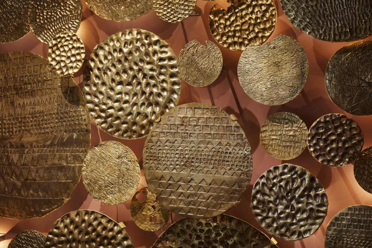 Detail of Ghana Pavilion at London Design Biennale featuring circular metal relief objects