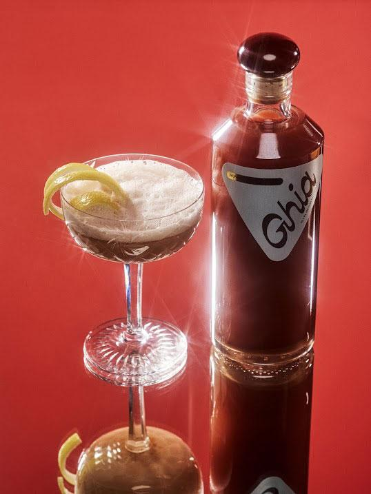 ghia red non-alcoholic drink against red background and next to cocktail glass
