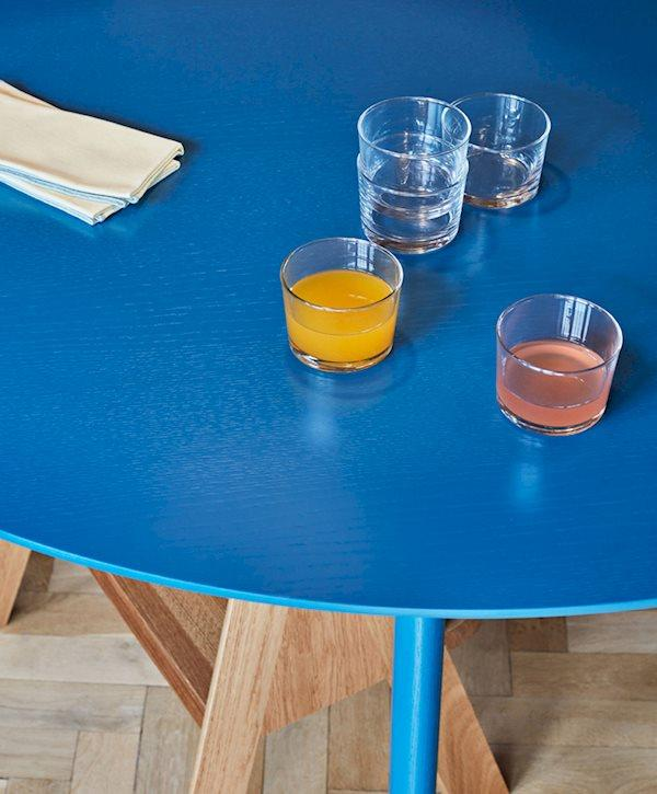Small glasses on a bright blue round table, by Hay