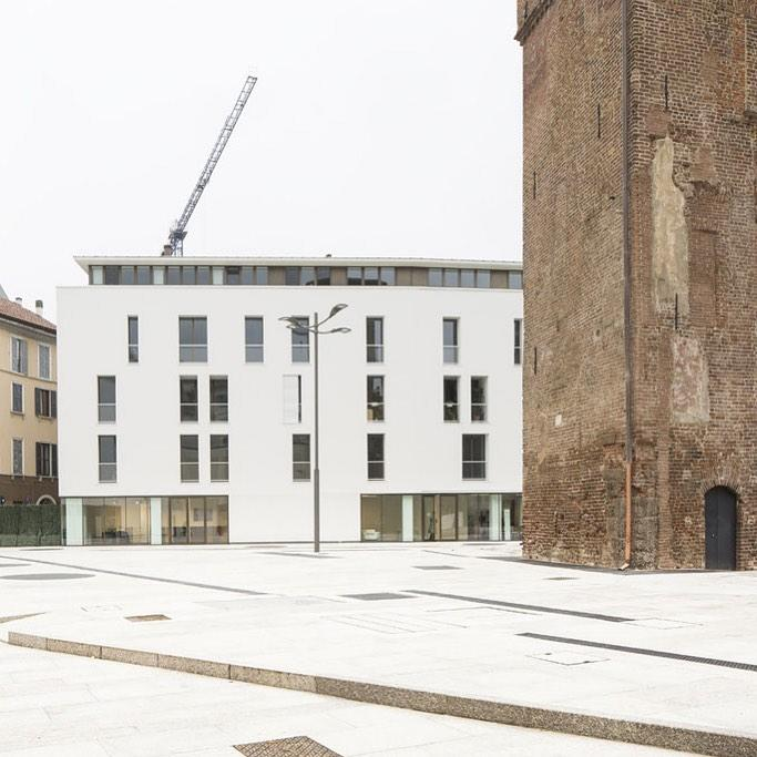A square with a contemporary white building next to a medieval tower in Milan Salone del Mobile 2021 - Discover Milan Design Week 2021