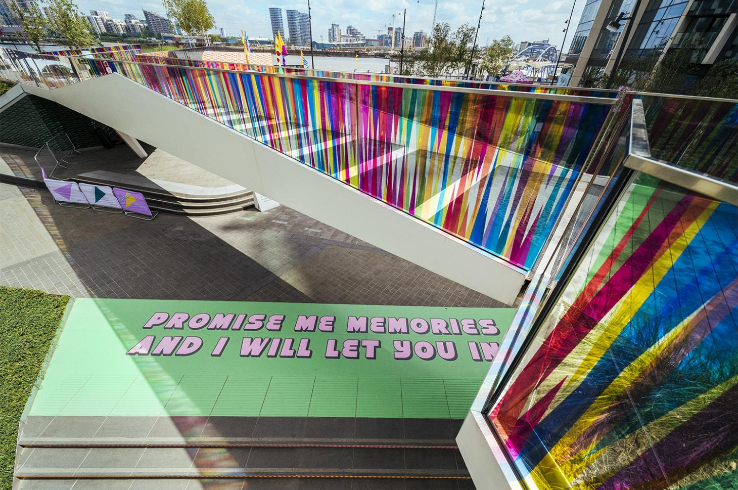 """A floor painting with the words """"Promise me memories and I will let you in"""" in pink type over a green background, created by Yinka Ilori for Greenwich Peninsula"""