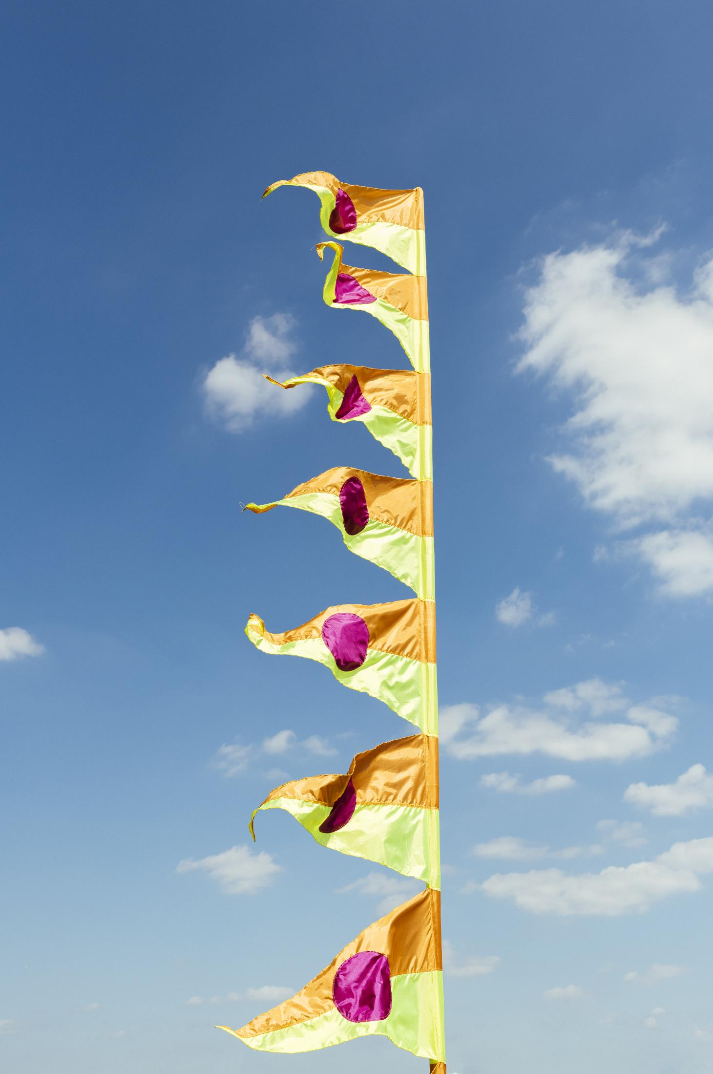 A colourful flag photographed against the blue sky, created by Yinka Ilori for Greenwich Peninsula