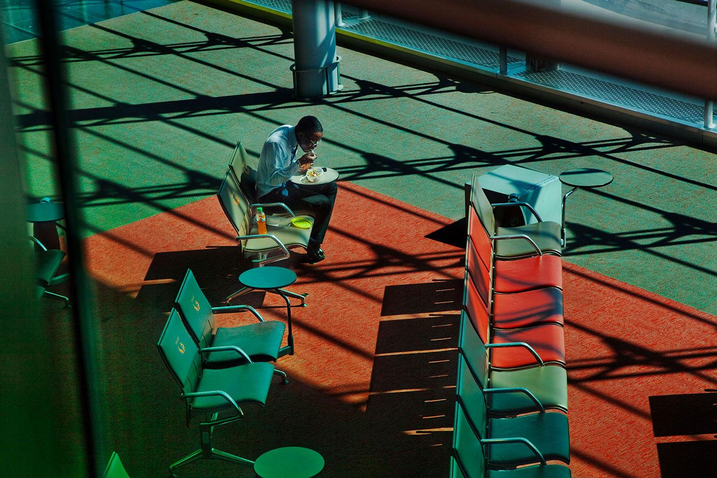 HarryGruyaert's photograph of a man eating a meal alone. Part of Magnum Photo's square print sale which focuses on Escapism