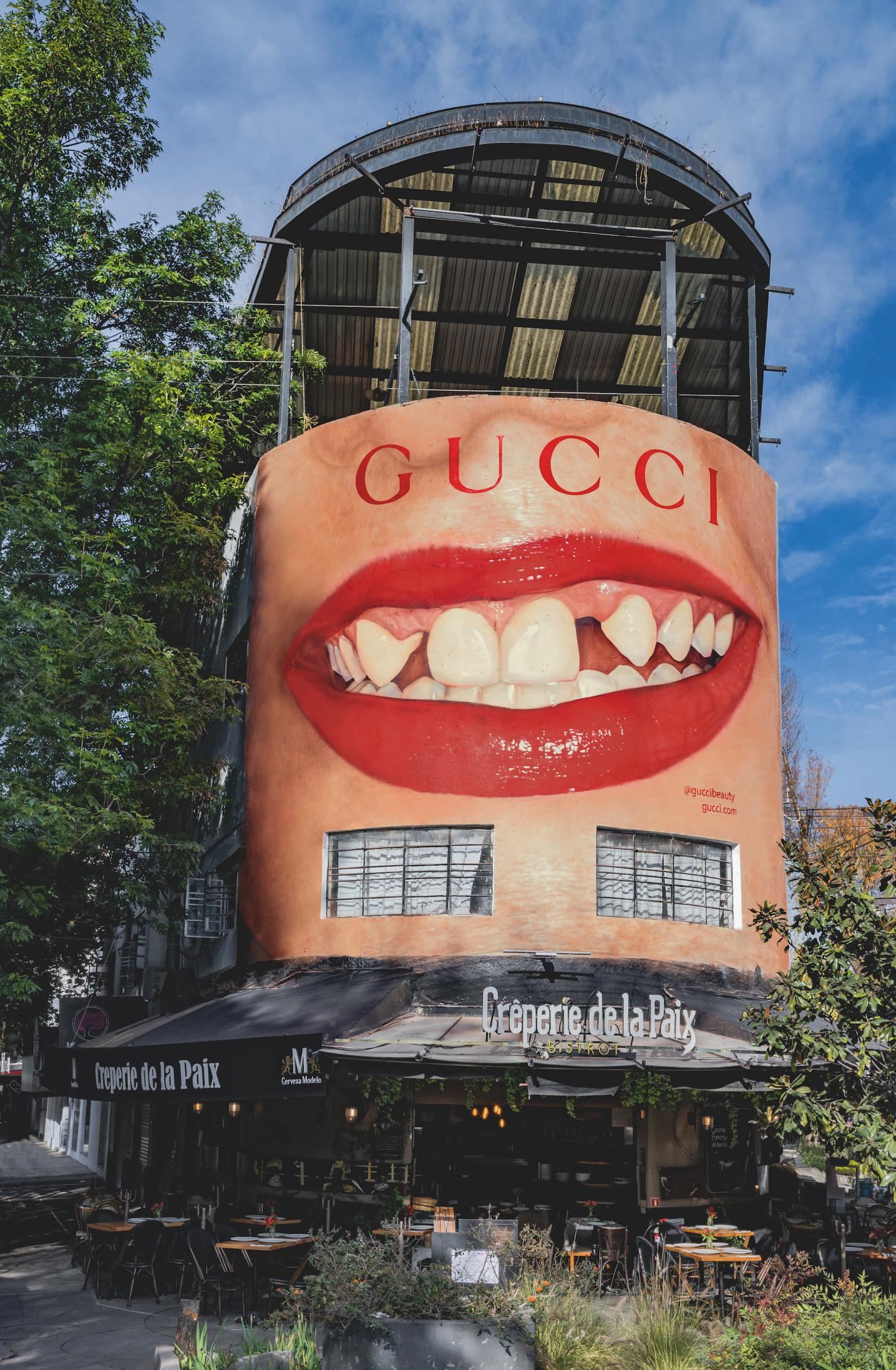 billboard displaying smiling red lips is situated above a cafe