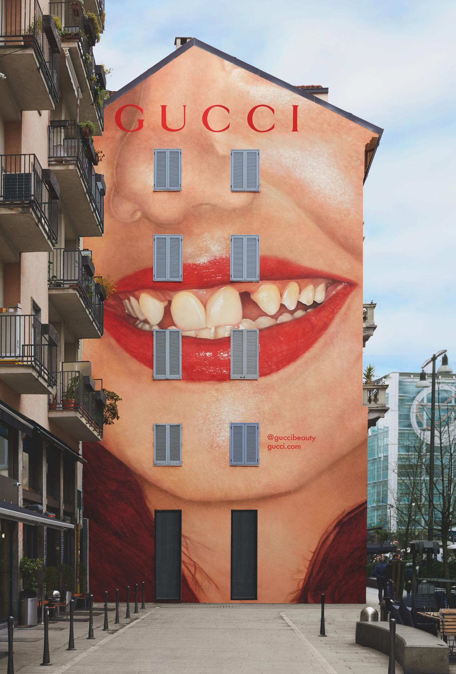 large painting of red lips on the side of a building