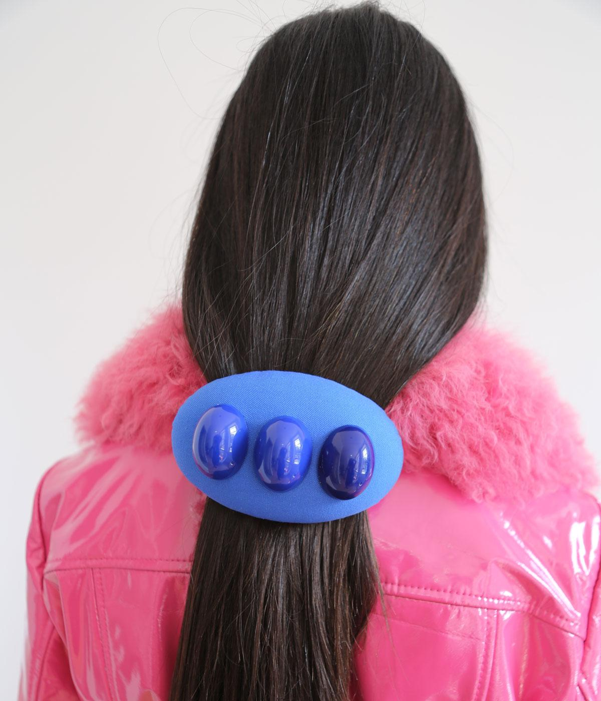 Woman's hair held back by a big blue clip