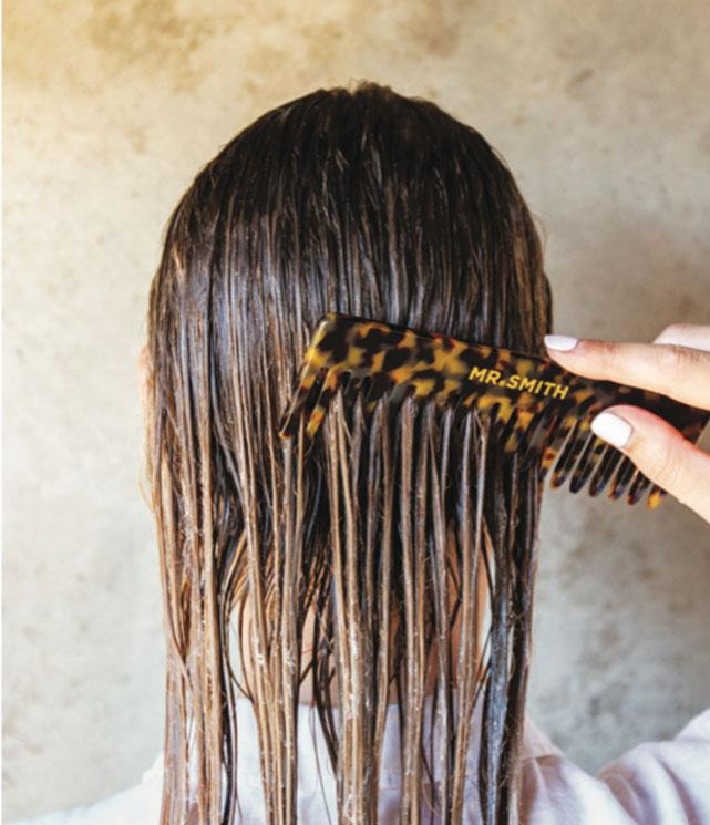 woman running mr smith tortoise shell comb through her hair