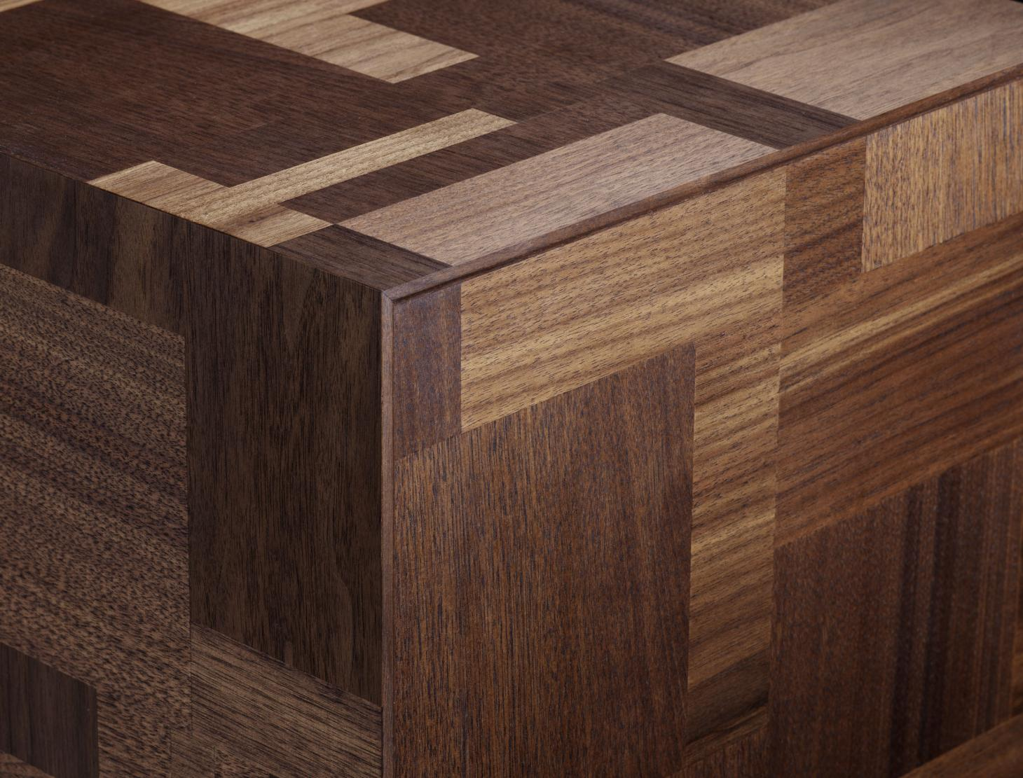 Detail shot showing a corner of a bedside table made of walnut and featuring an intarsia patterned motif