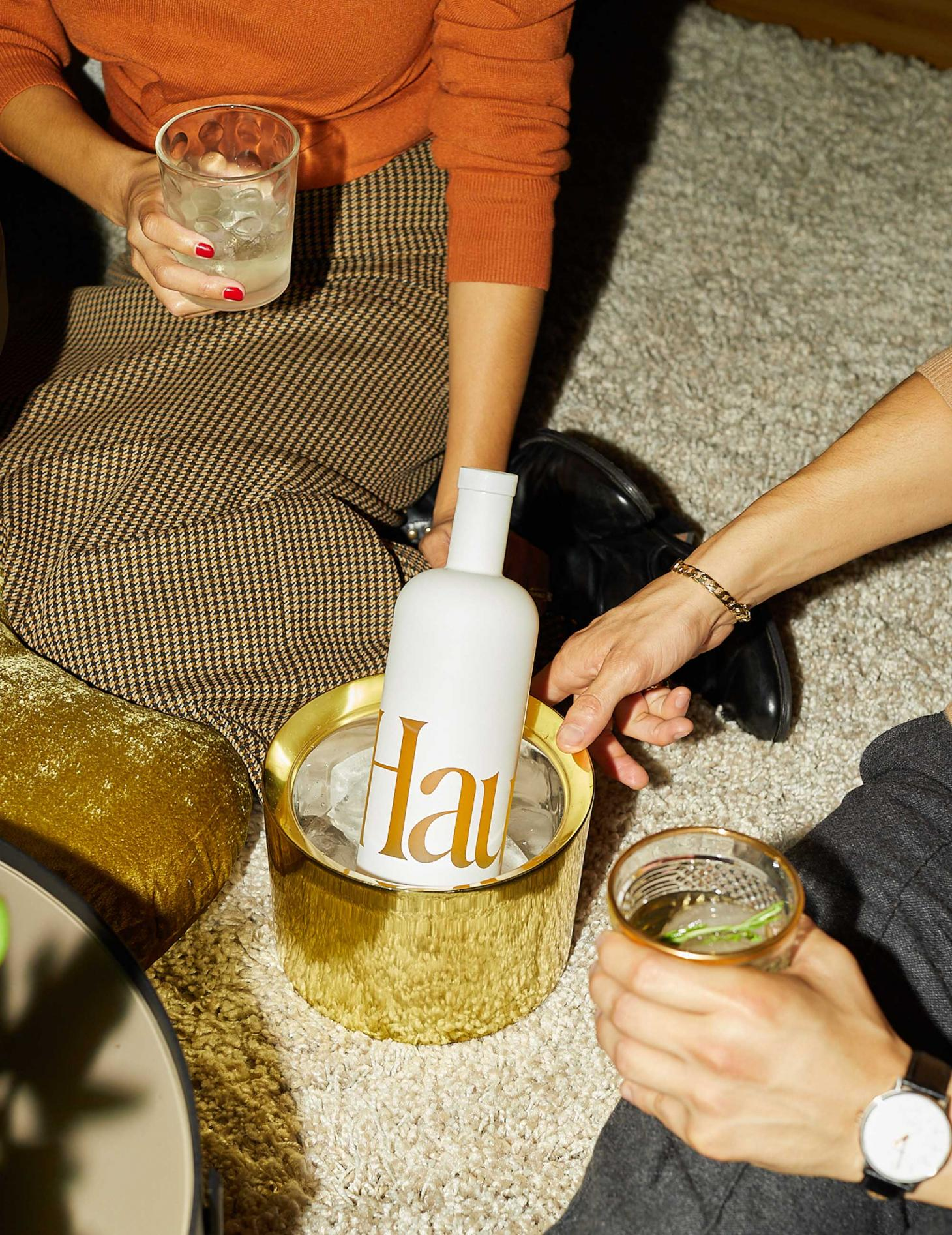 Haus bottle in cooler with people drinking.