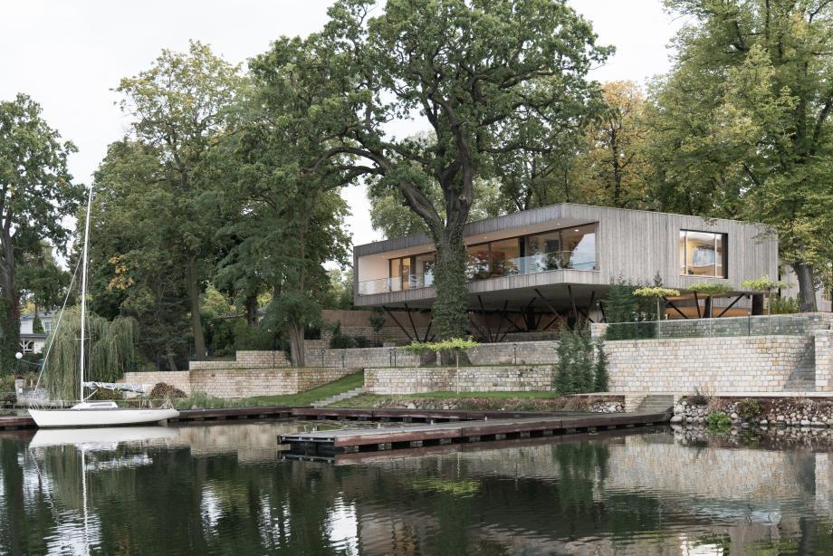 this modernist-inspired wood-clad home sits by a lake