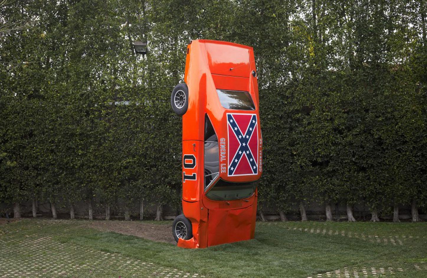Hank Willis Thomas, A Suspension of Hostilities, 2019. A red car nose down featuring the Confederate Flag on its roof