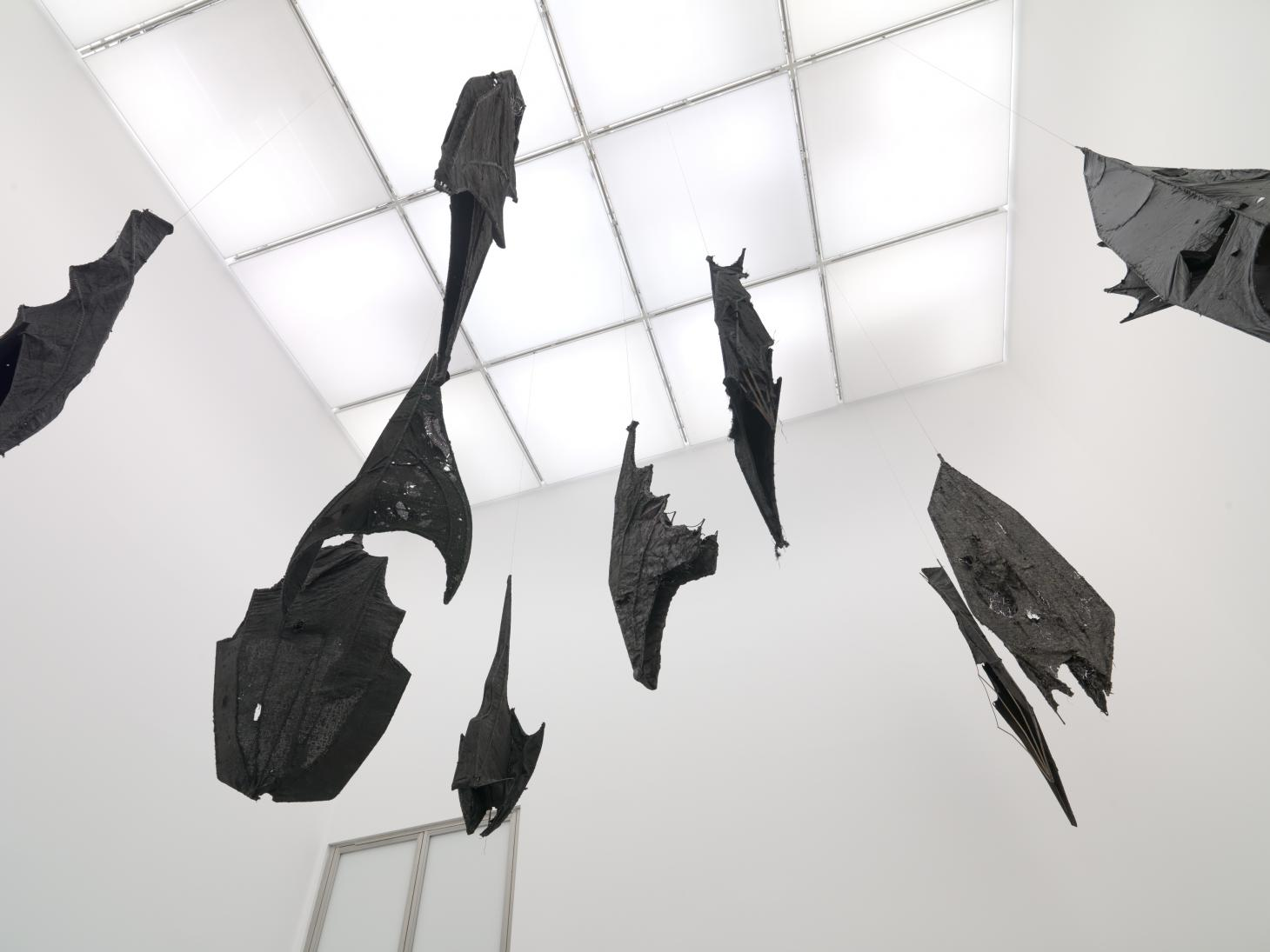 Black artwork bats hang from white ceiling at White Cube, exhibition by Ibrahim Mahama