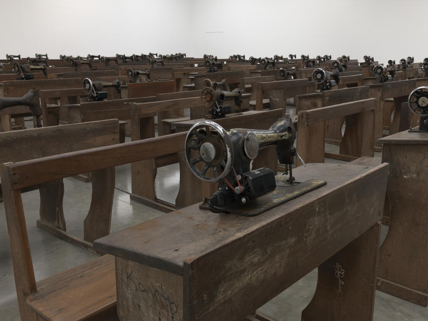 Close up of wooden desks and tables with sewing machines, installation at White Cube, by Ibrahim Mahama
