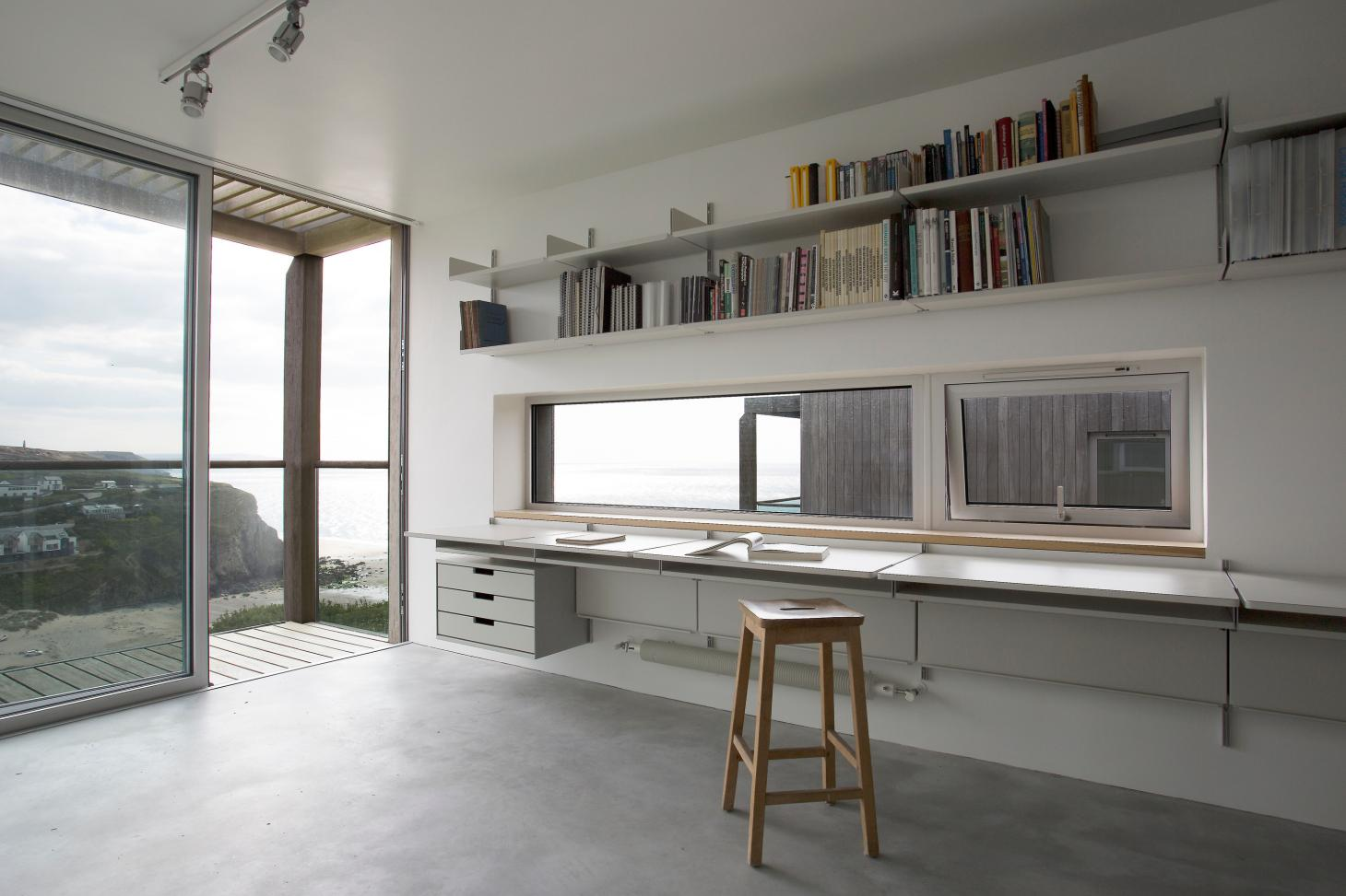 Vitsoe shelving with desks by Dieter Rams installed in office with large window overlooking a beach
