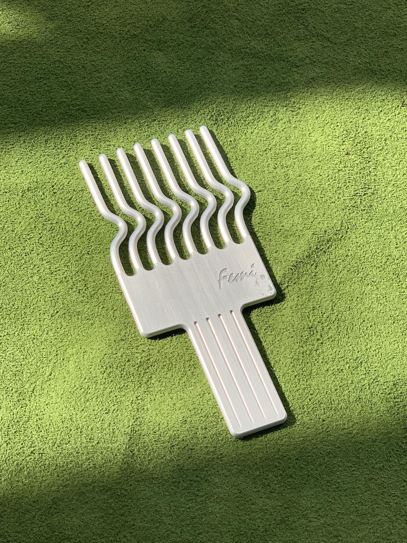 white afropick against a green background