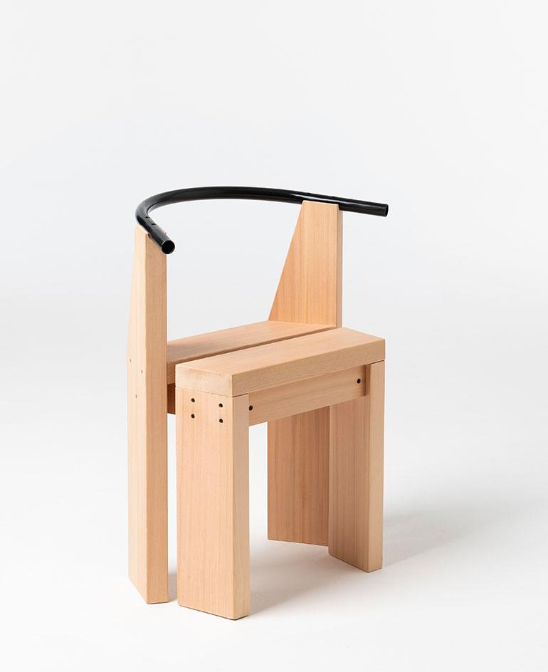Chair made of natural wooden parts with black curved back