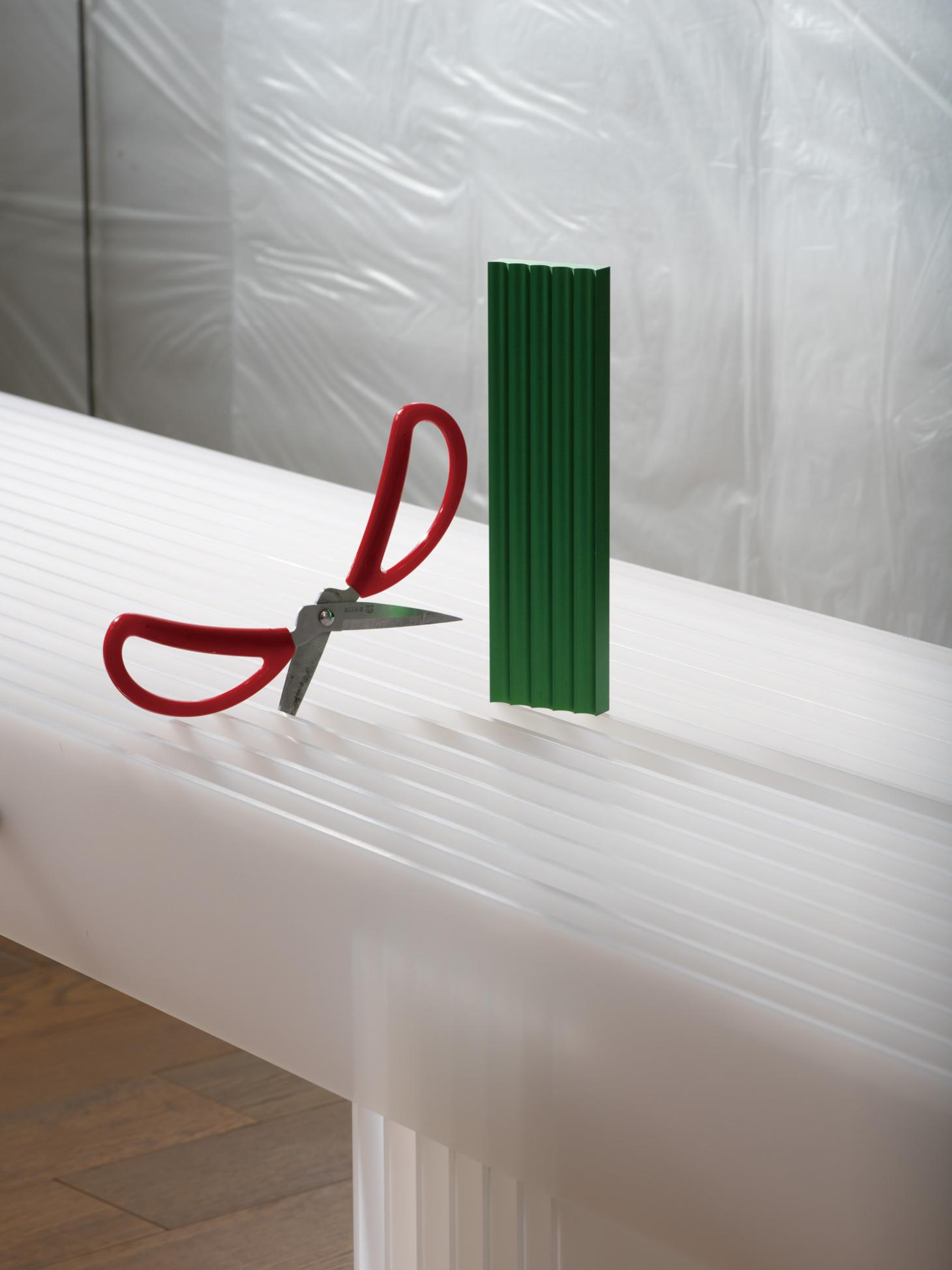 A red pair of scissors and a green aluminium pen rest from the 'Components' series by Mario Tsai are displayed on a 'Grid' bench