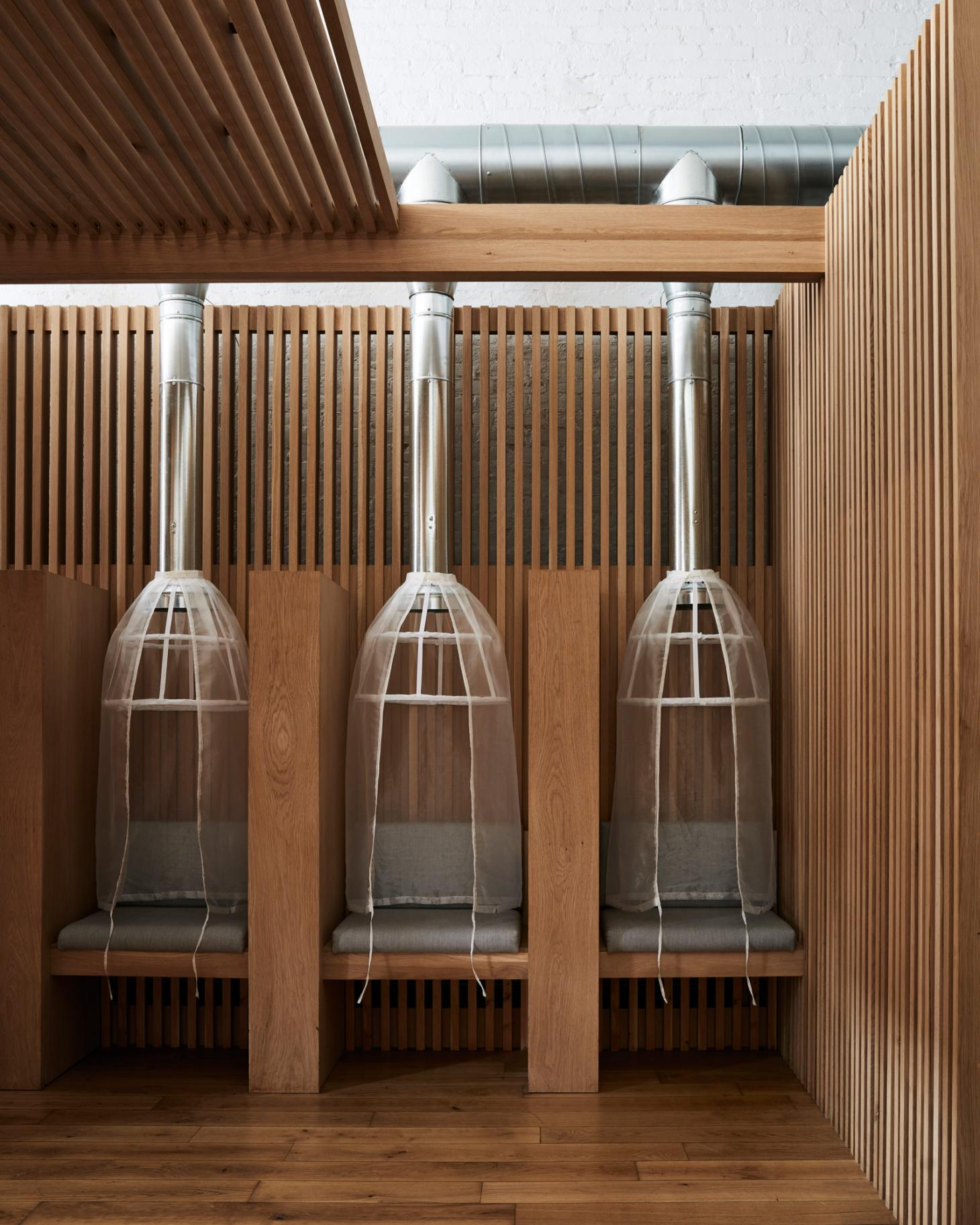 the wood-clad interior of a Tribeca hair salon featuring seating pods with gray cushions