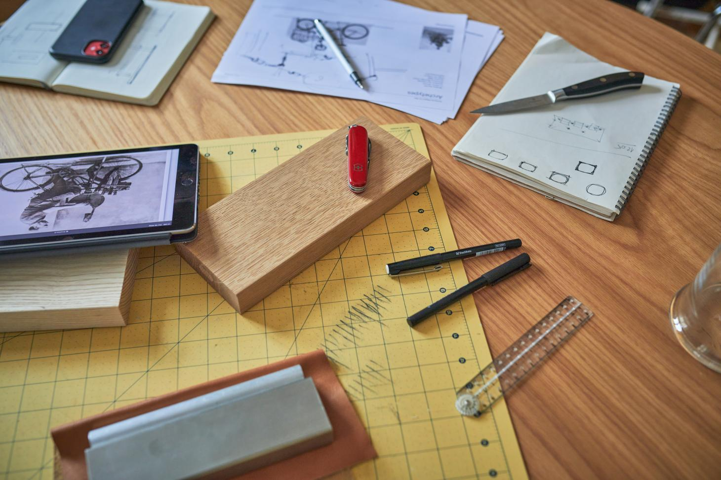 Sketches and photographs on a desk at Jenkins and Uhnger's studio, including a series of Victorinox knives as part of their project development