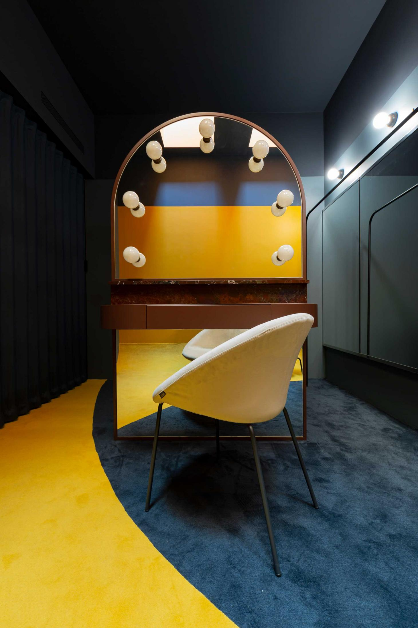 A changing room at Teatro degli Arcimboldi, Milan, featuring a white chair on yellow carpet in front of a mirror