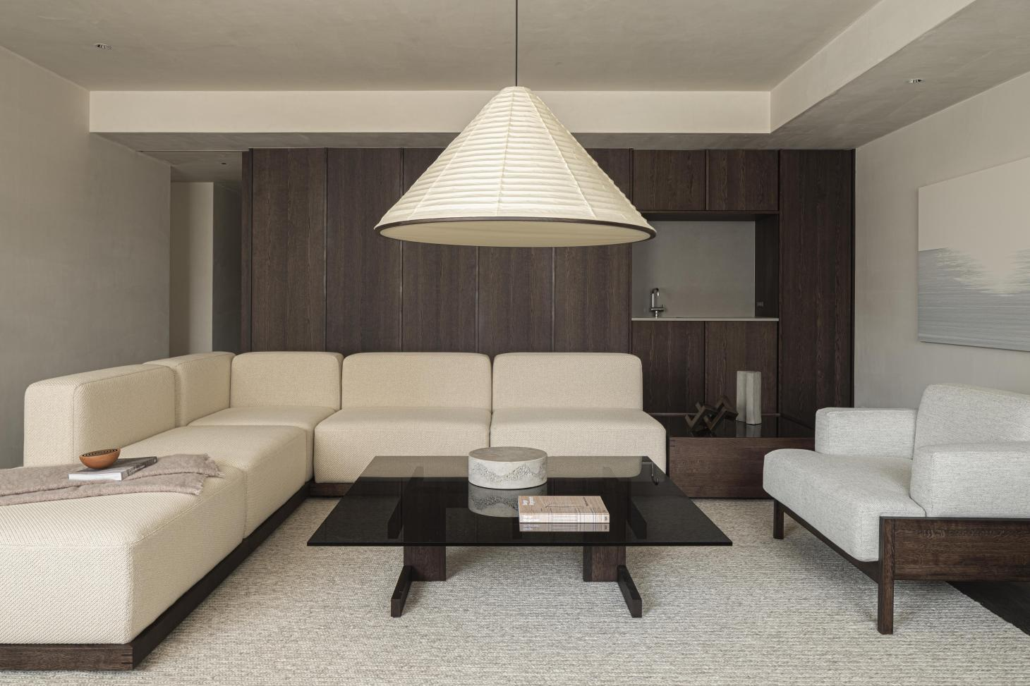 A living room in the Karimoku Case Study house furnished with cream corner sofa and pendant lamp