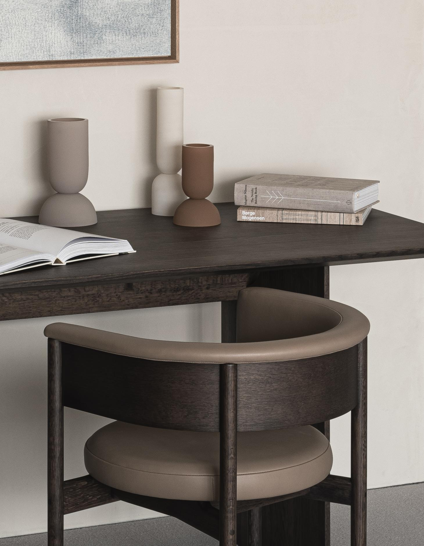 A home office corner in the Karimoku Case Study house features a circular chair and dark wooden desk