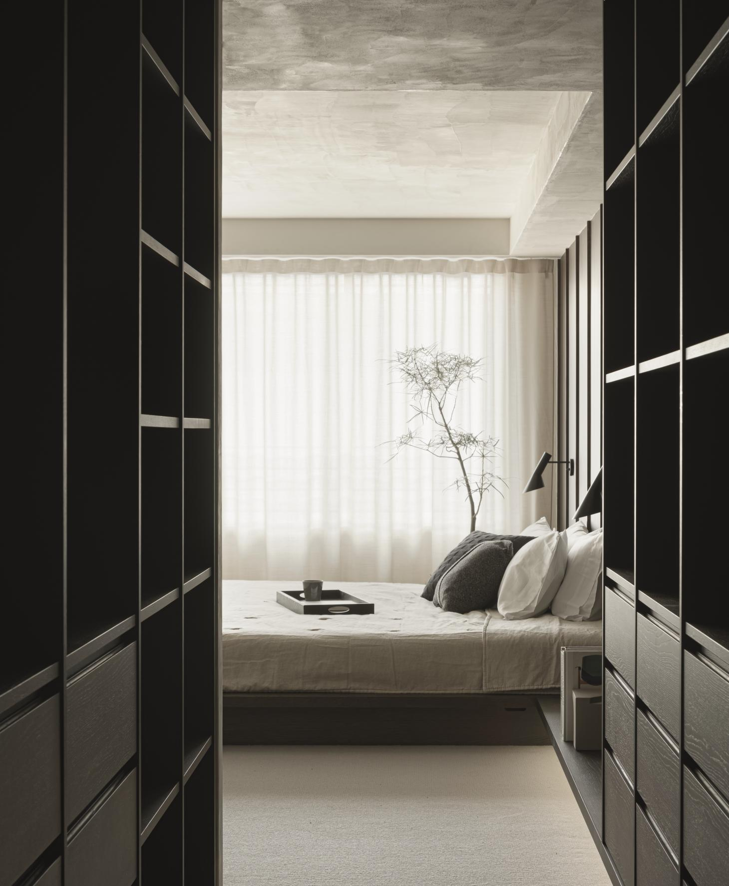 A view of the bedroom from the walk in wardrobe clad in dark wood