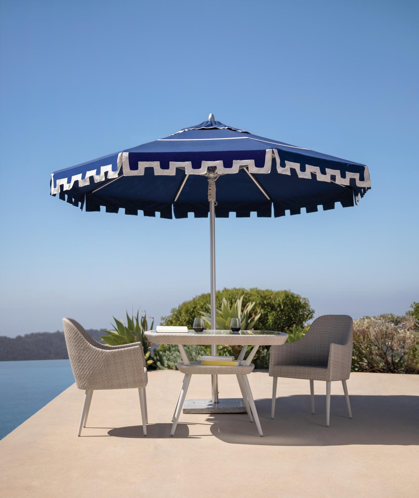 Classic parasol in blue and white on a terrace by the sea