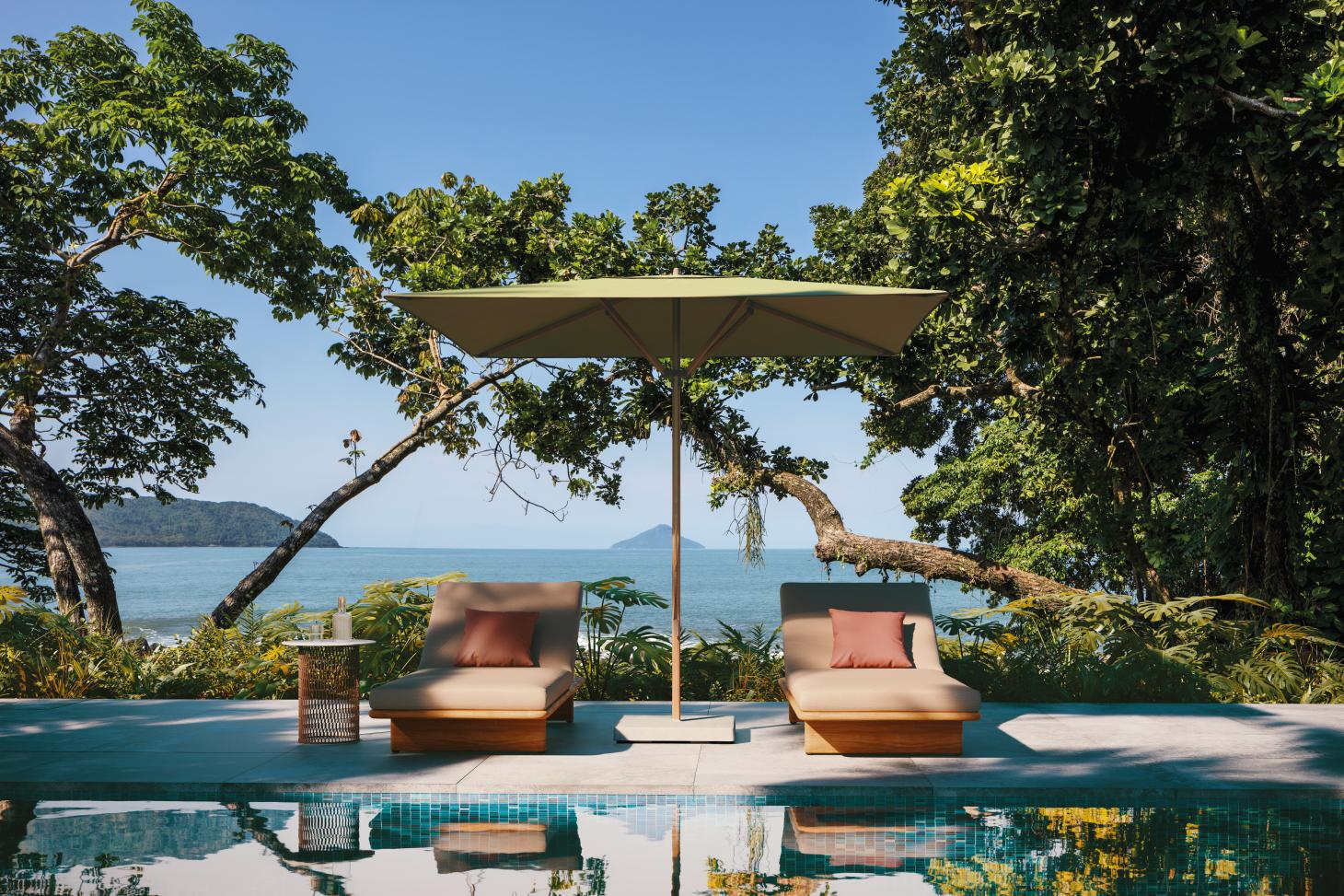 Orange Parasol by Kettal photographed poolside with countryside on the background