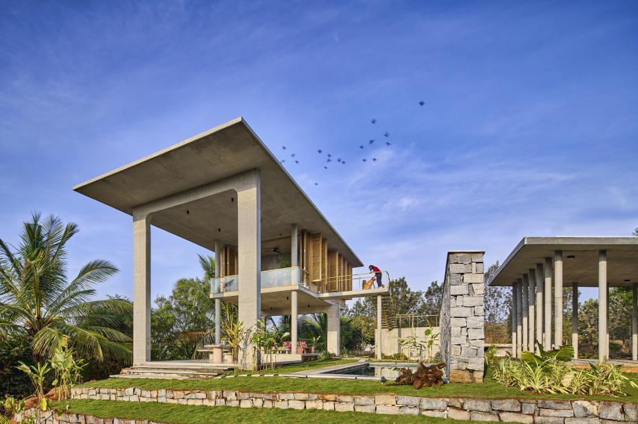the sculptural open concrete spaces in this India home helps it commune with nature