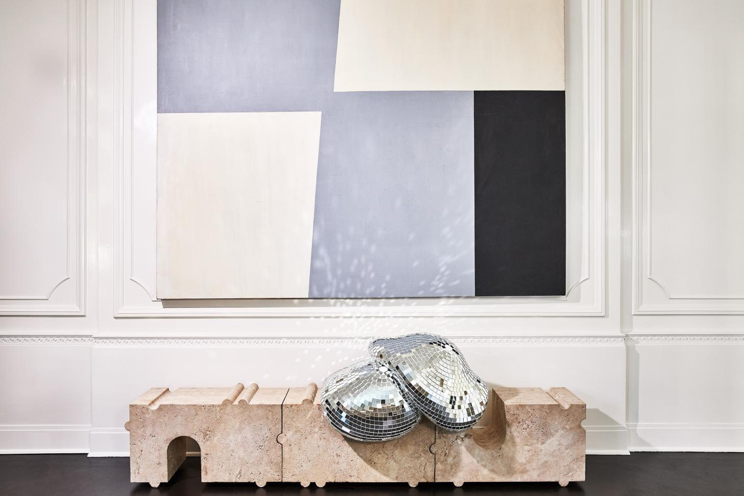 Two melted disco balls on a marble bench, designed by Rotganzen for the Kelly Wearstler shop