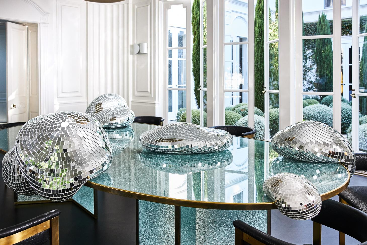 Seemingly melting disco balls on a table, speciall edition of Quelle Fête by Rotganzen for the online Kelly Wearstler shop