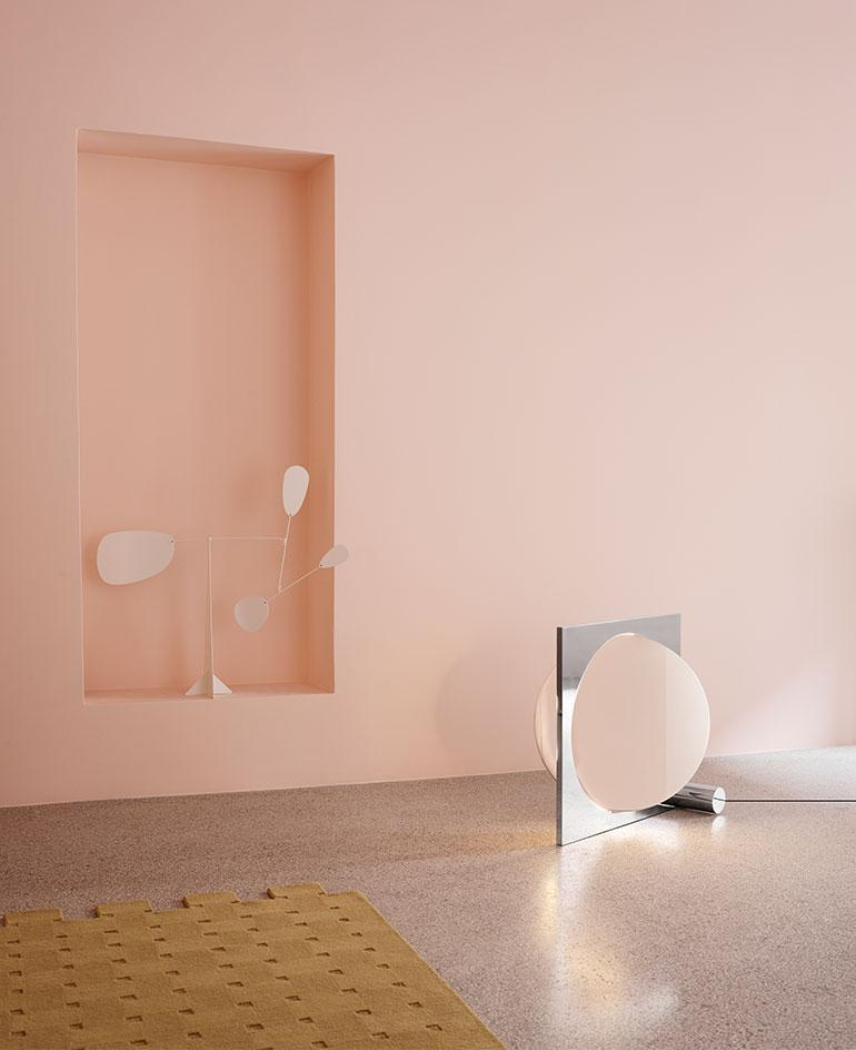 A pink room featuring a silver floor lamp by Louis Poulsen with a rotating disc concealing the light source. When the disk rotates, the light effect is that of moon phases