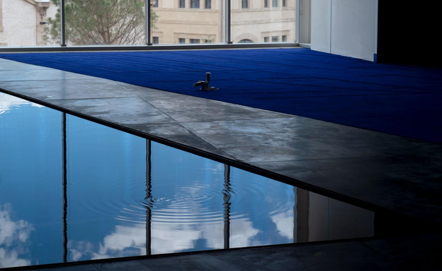 A swimming pool pictured against a glass window
