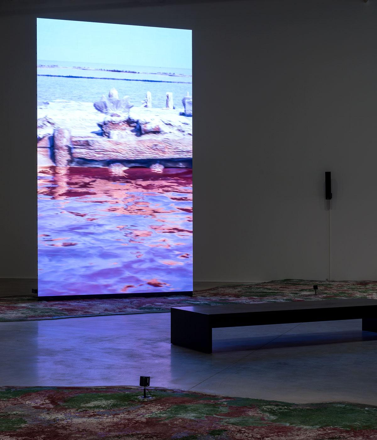 A screen with the sea on inside a gallery space