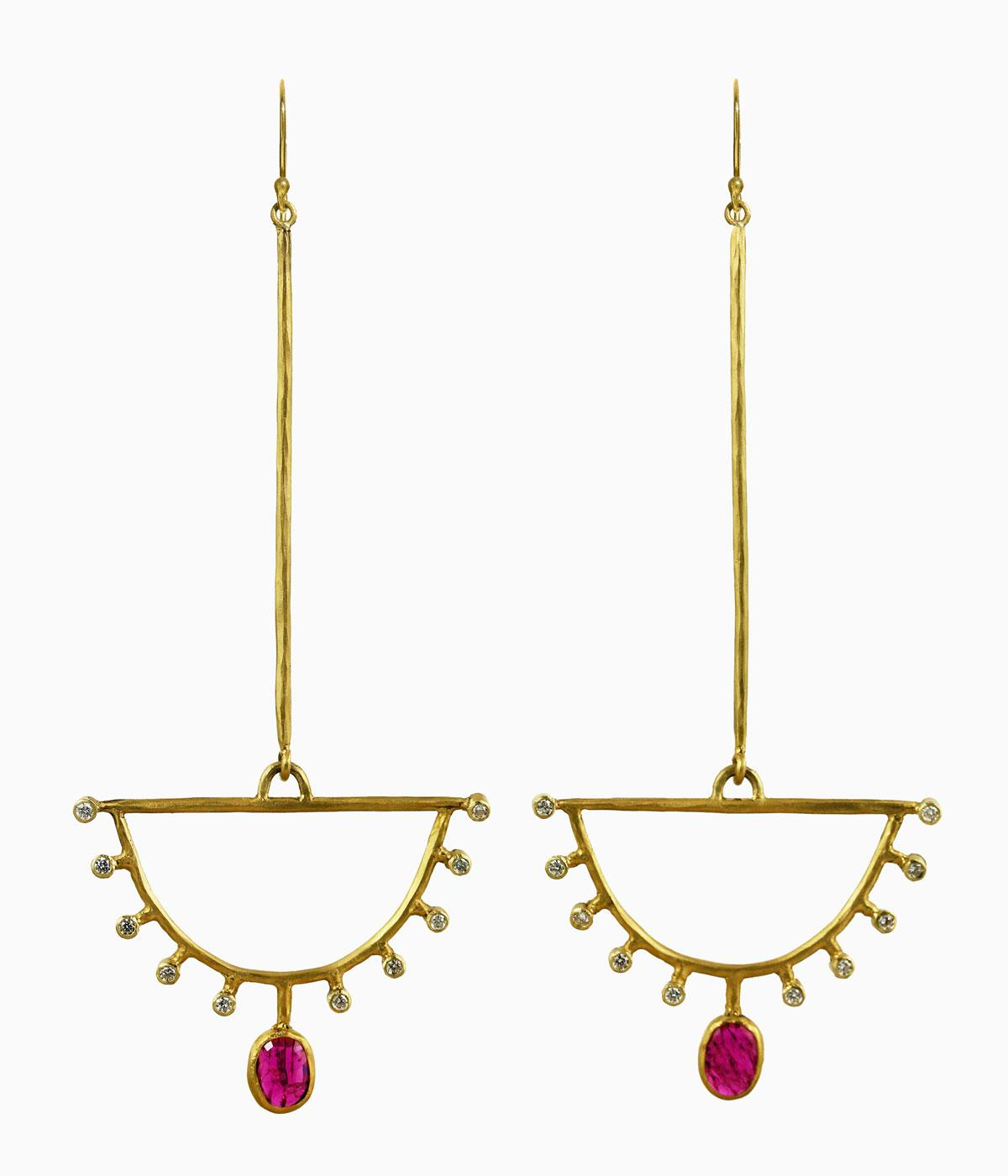Gold dangly earrings with rubies hanging from them