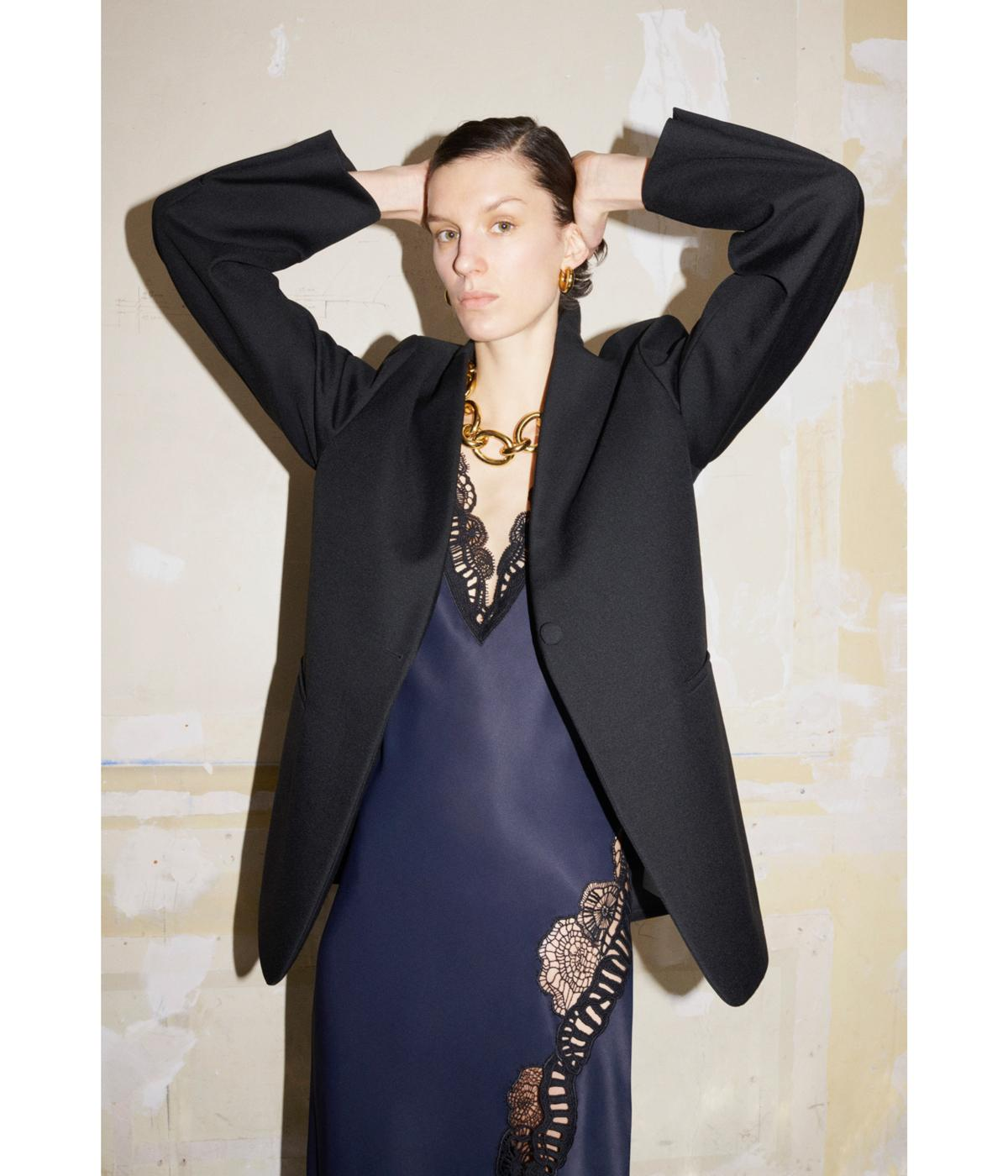 Woman wearing slip dress and suit jacket
