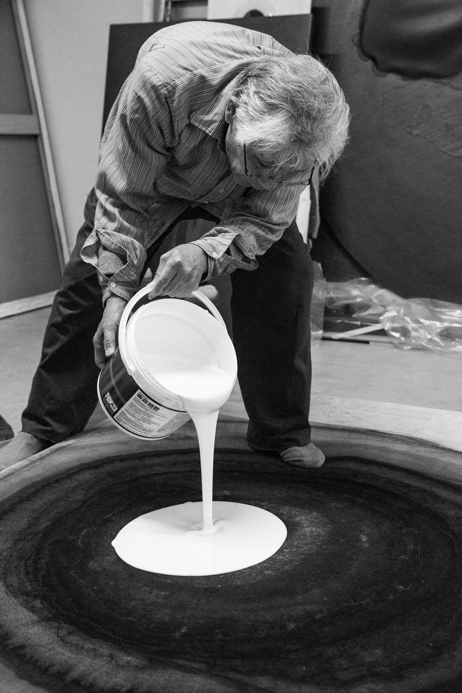 Portrait of Japanese artist Takesada Matsutani in the studio pouring vinyl glue onto a work in 2019 ahead of an exhibition at Hauser & Wirth Hong Kong.Photographer Michel Lunardelli