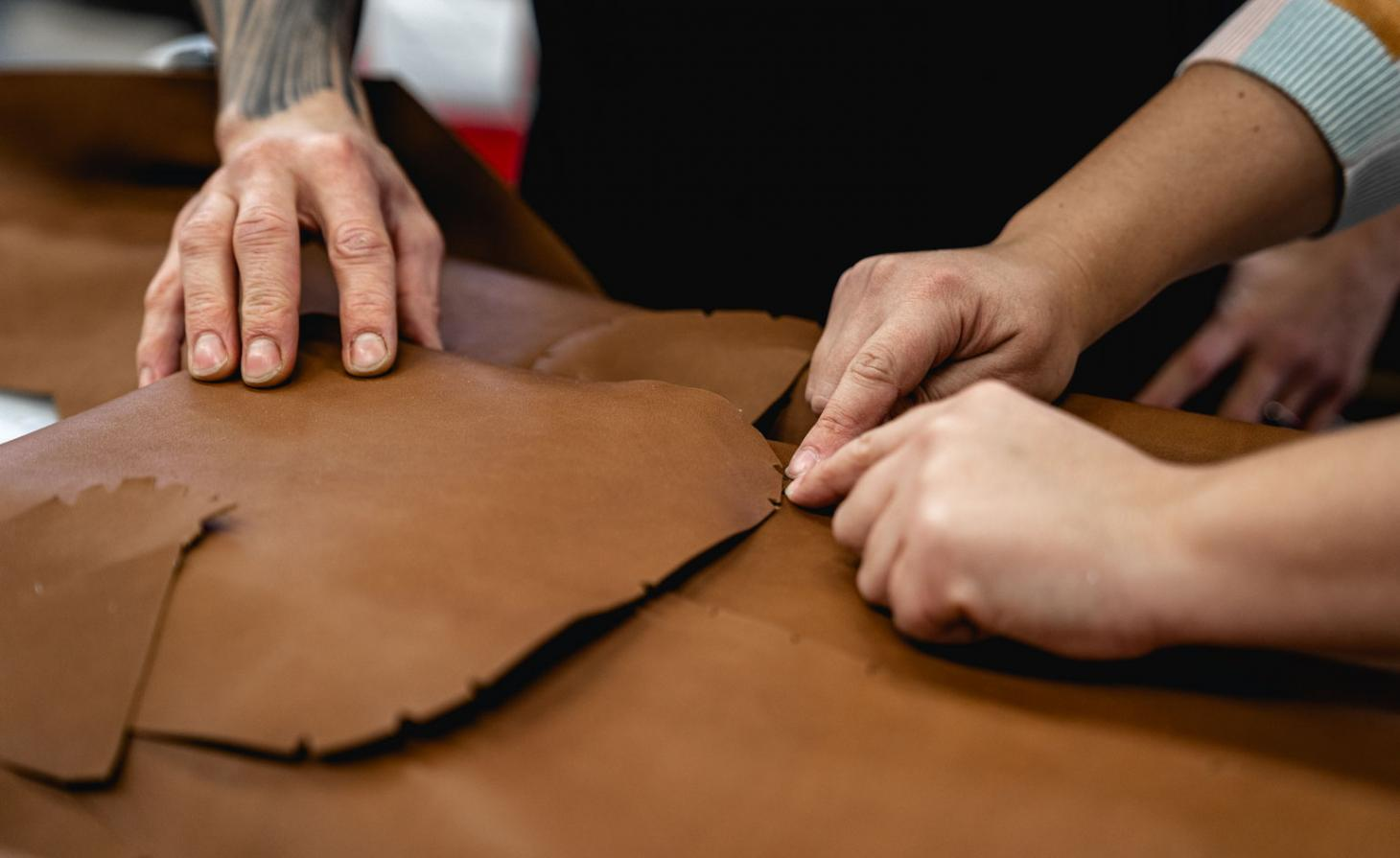 A man's hand cutting brown leather