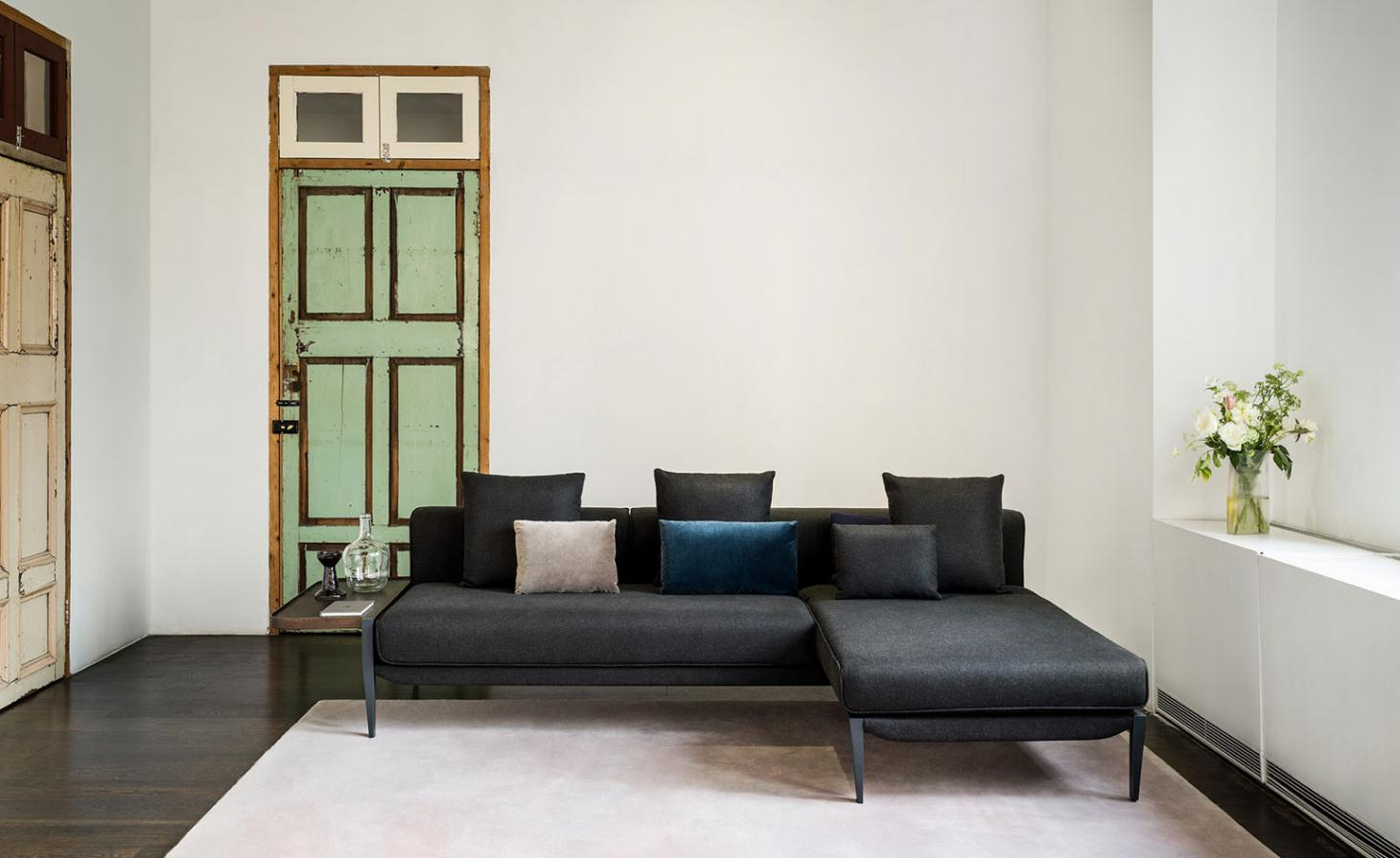The sofa designed by Michele De Lucchi for Stellar Work is shown here with charcoal upholstery. The sofa is photographed on a cream coloured rug and with a green door in the background