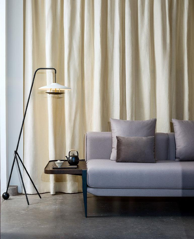 The Float sofa by Michele De Lucchi for Stellarworks photographed against the backdrop of a white curtain, and with a floor lamp next to it. The sofa is upholstered in light grey fabric with grey cushions
