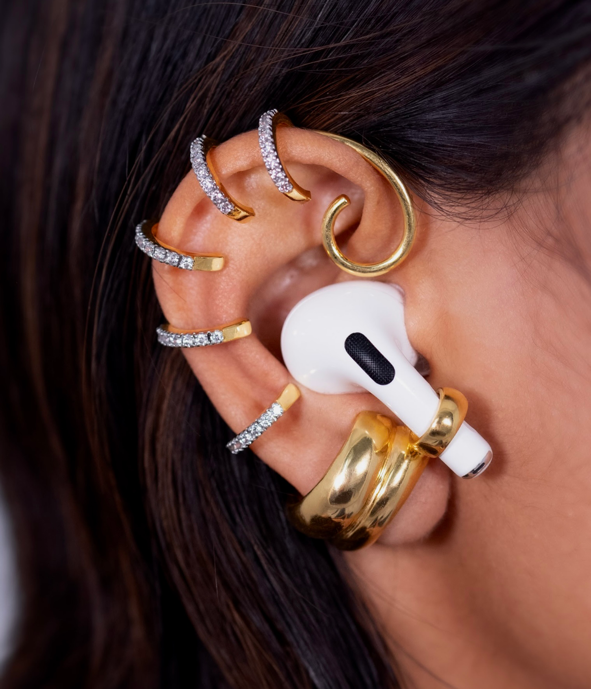 Woman wearing AirPod with earring on it
