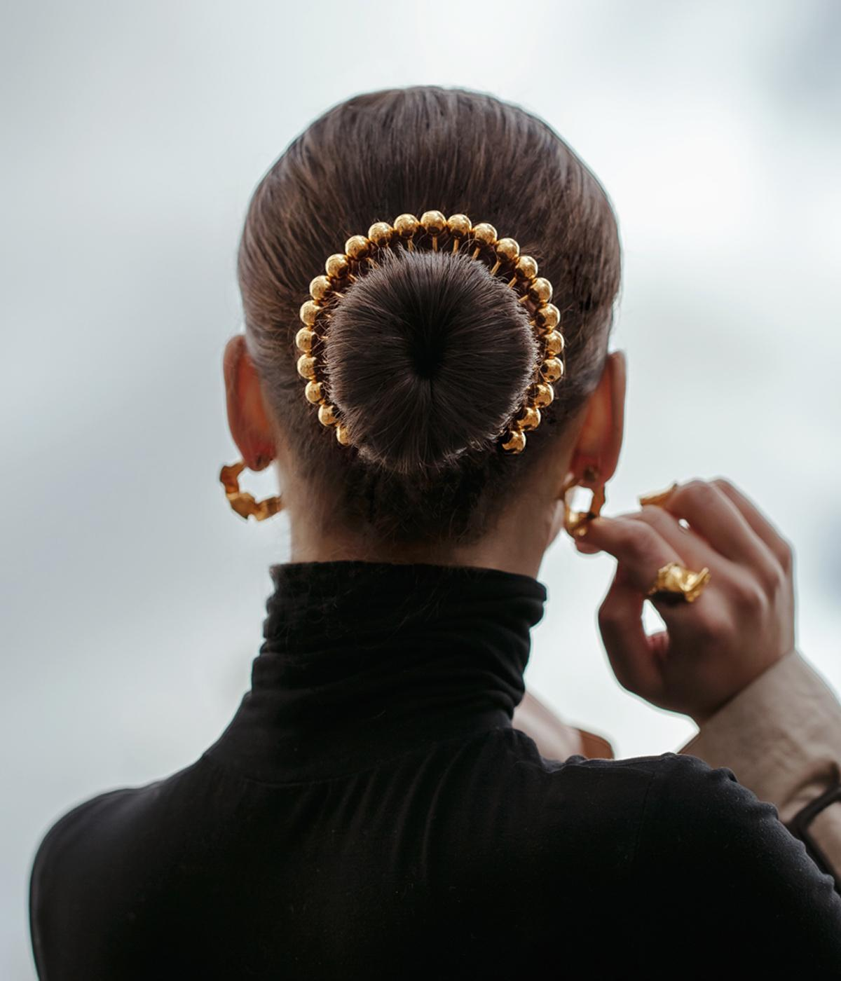 Back of woman's head, hair held back with a gold jewel