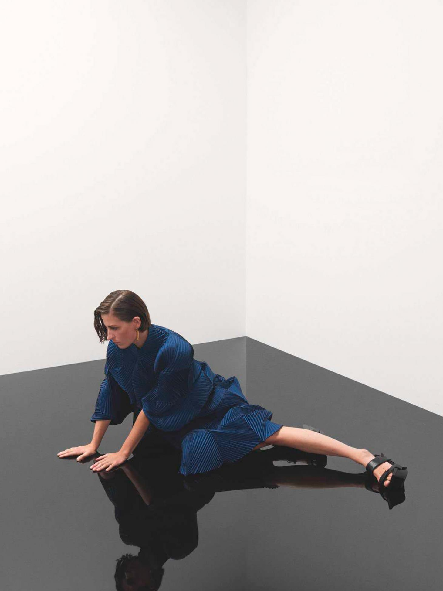Image of woman in blue Issey Miyake pleats dress on black shiny floor