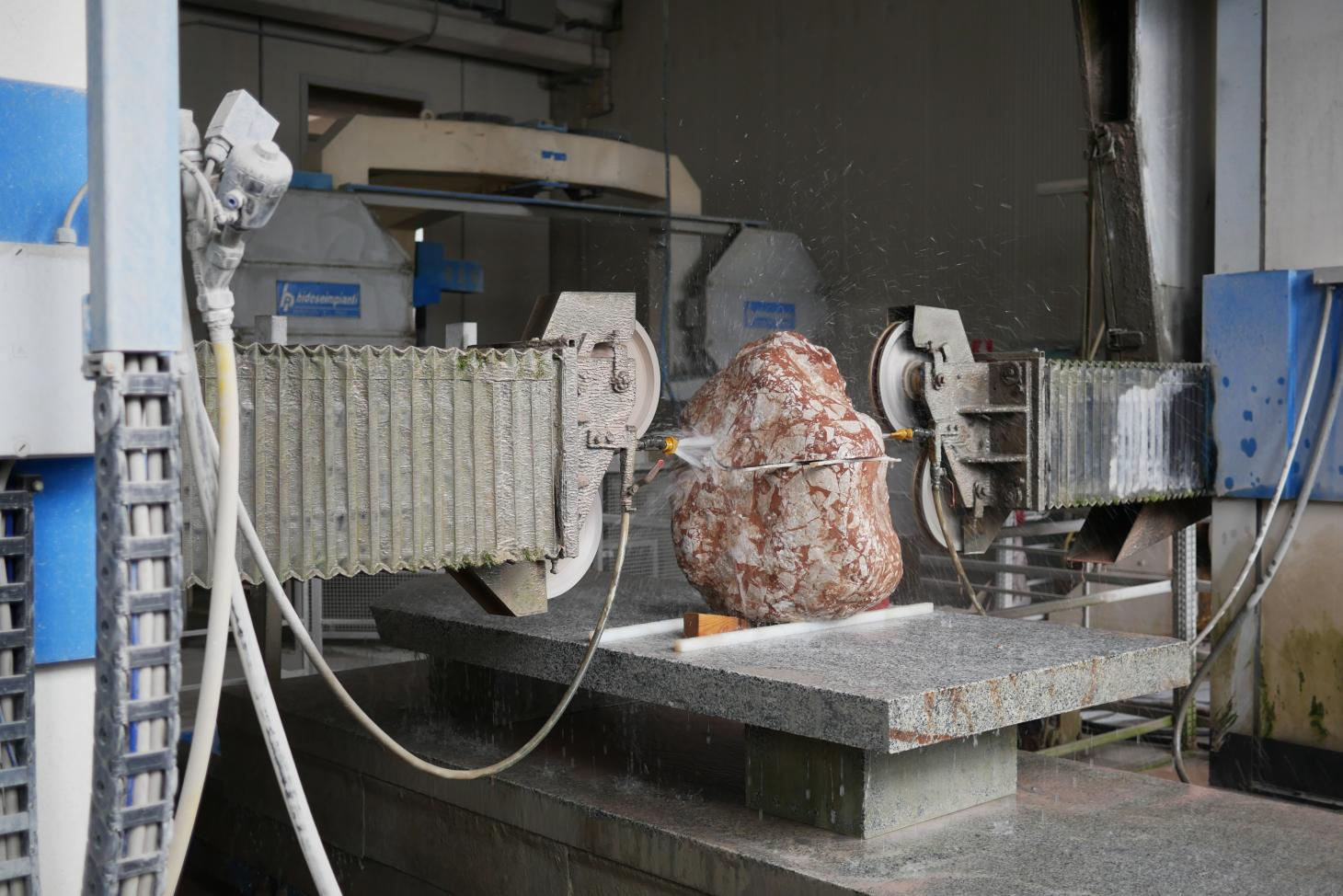 Large red stone with white speckles being cut by a machine to become a chair