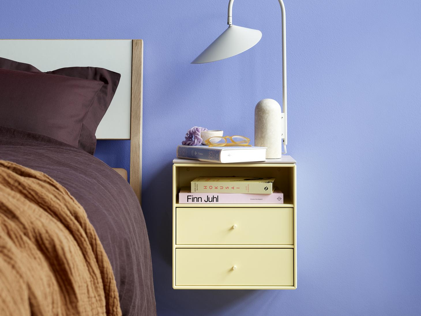 Yellow bedside table from the Montana Mini collection installed on blue wall in a bedroom