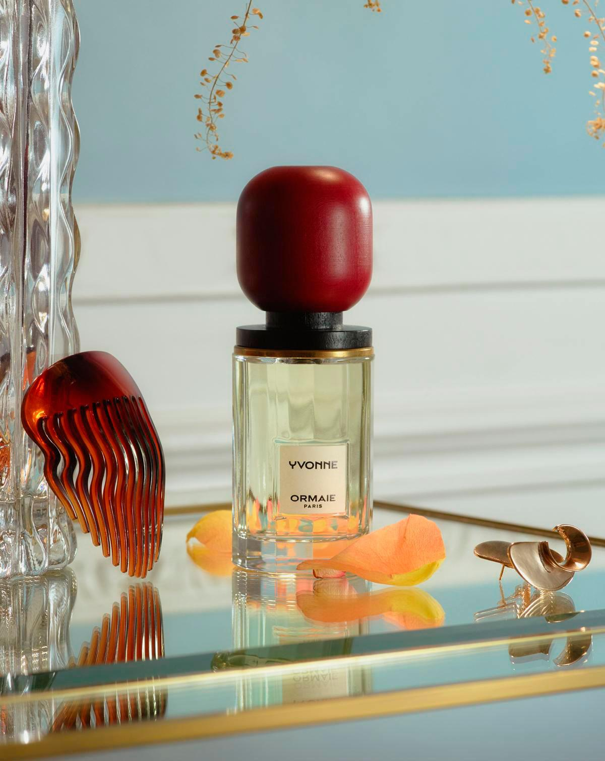 Ormaie bottle of Yvonne fragrance a glass countertop against a light blue wall