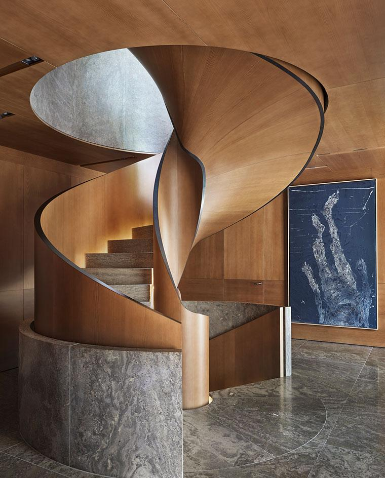 A wooden spiral staircase and marble floor in an interior shot from the book on Christian Liaigre design work