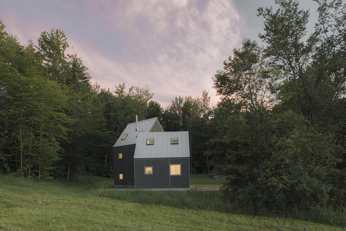 dusk view of timber clad Vermont cabin in the countryside