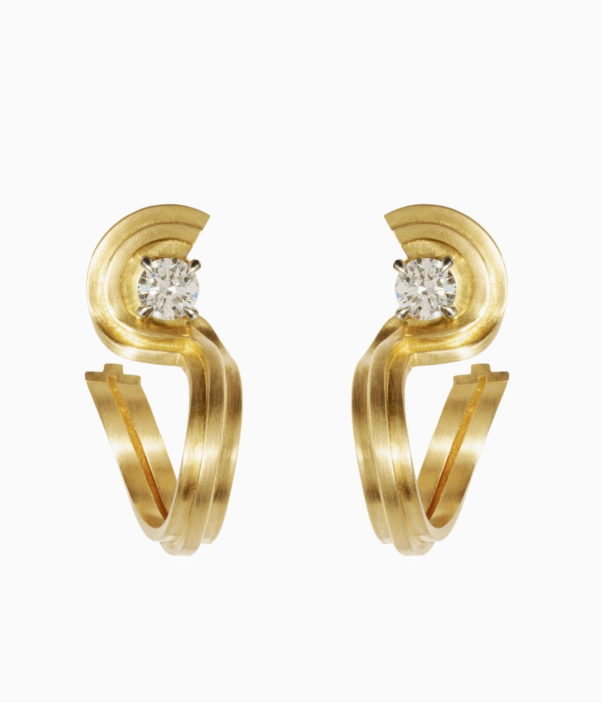 Gold curved earrings each with a single diamond